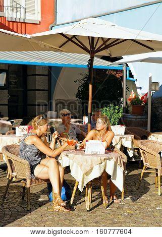 People Relaxing In Street Restaurant In Ascona Town In Swiss