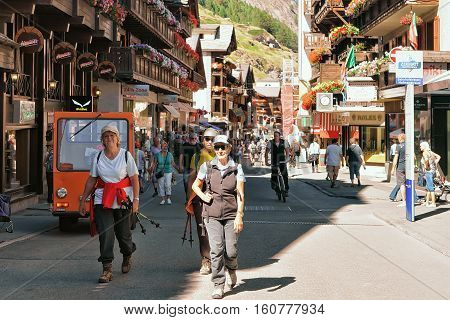 Tourists Doing Nordic Walking At City Center In Zermatt