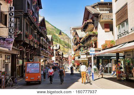 Tourists Doing Nordic Walking At City Center Of Zermatt