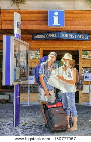 Tourists Looking Into City Map At Tourist Offcie Of Zermatt