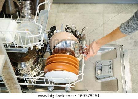 The woman pushed the dirty dishes in the dishwashing machine.