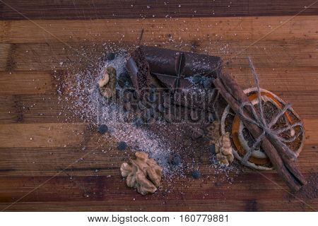 composition of chocolate, sugar, nuts and dried oranges on a wooden board