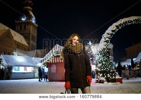 Long hair girl on European Christmas Market. Young woman Enjoying Winter Holiday Season. Blurred Christmas Lights background, dusk. Cups with drink in hand. Selective focus