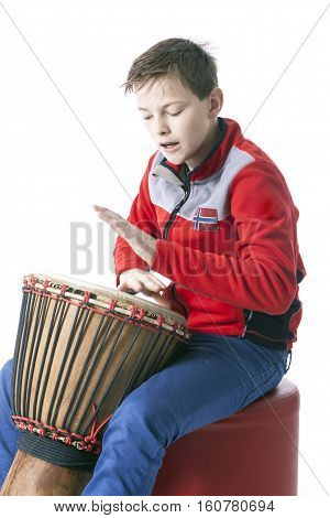 teenage caucasian boy plays the djembe in studio with white background