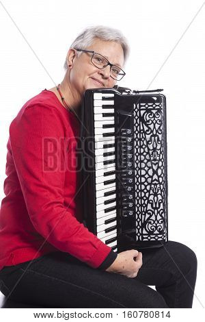 older caucasian woman with glasses plays accordion in studio with white background