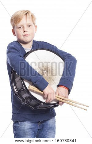 young blond boy in blue outfit holds drum against white background in studio