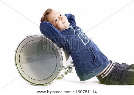 teenage boy sits against drum in studio with white background
