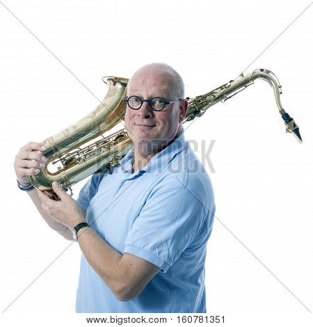middle aged man in blue carries tenor saxophone on shoulder against white studio background