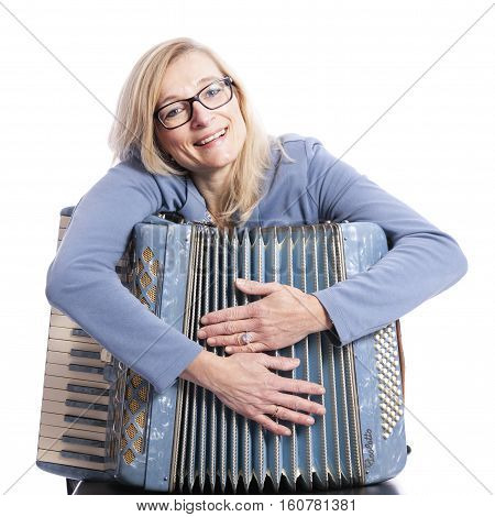 blond woman in blue with glasses holds accordeon and smiles in studio with white background
