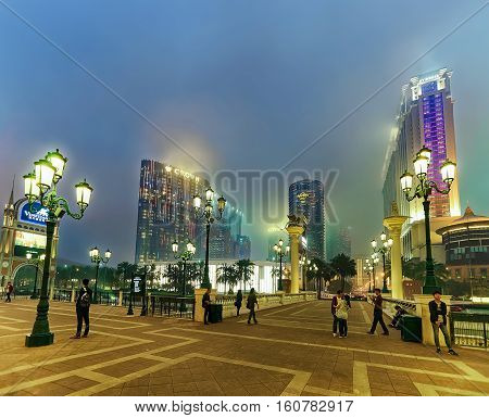 Macao China - March 8 2016: Embankment of Venetian and City of Dreams Macau Casino and Hotel luxury resort in Macao China. Late in the evening. City of Dreams and People are on background
