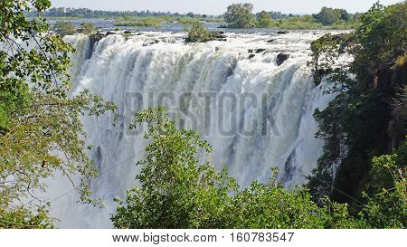 View to the Victoria Falls from Zambia, water masses fall into a canyon