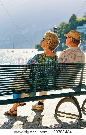 Ascona Switzerland - August 23 2016: Senior Couple sitting on the bench at the embankment in Ascona on Lake Maggiore Ticino canton Swiss