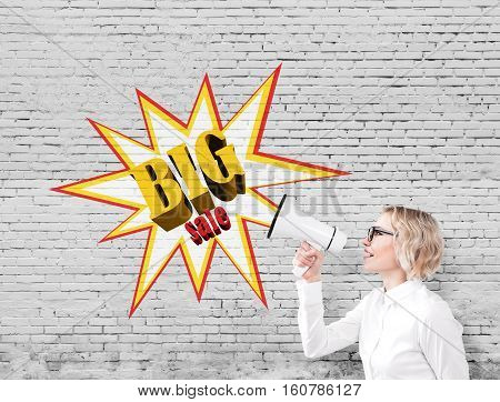 Side view of a blond woman with short hair wearing glasses and holding a megaphone standing near a brick wall with a big sale poster on it. Mock up