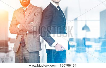 Two business partners are standing together in an office. One is holding a laptop. The second is standing with arms crossed. Cityscape. Toned image. Mock up. Double exposure