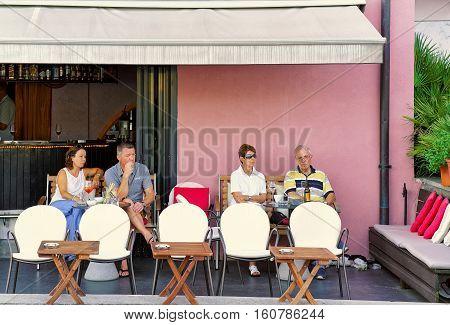 People Relaxing In Street Restaurant In Ascona Town Of Swiss