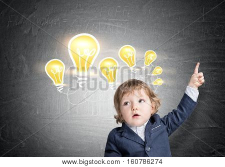 Portrait of an adorable baby boy in a blue suit pointing upwards while standing near a bright light bulb sketch drawn on a blackboard.