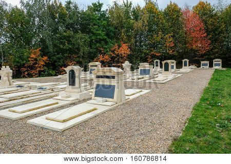 This shot shows plots in a cemetery made of white limestone and with plaques. Taken in the autumn and shows some lovely colours in the trees and bushes.