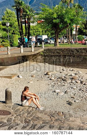 Woman Sitting On The Shore At Ascona Expensive Resort