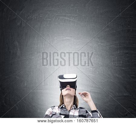 Woman in virtual reality glasses and a flannel shirt is standing near a blackboard and looking upwards. Mock up