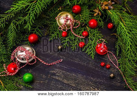 Christmas festive frame with Christmas tree and jinglebells on dark background with copyspace