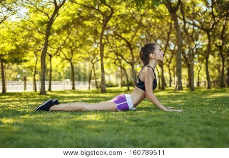 Beautiful girl doing cobra pose on the grass outdoors sport yoga stretching healthy lifestyle. Exercise for the back.
