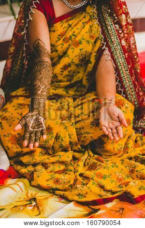 Indian Bride in the occasion of a wedding ceremony in an event Mehandi. Traditional mehndi design on Indian women's hands