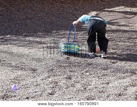 A little boy dressed in his sunday Best bends over to pick up the egg he found during an Easter Egg Hunt on Easter Sunday in Central Oregon.