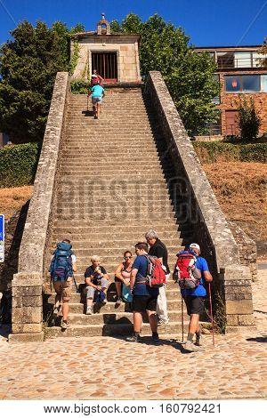 PORTOMARIN SPAIN - AUGUST 12: Pilgrims ascending the Roman staircase on August 12 2016