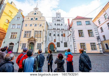 Riga, Latvia - September 22, 2016: View in the famous three brothers houses with group of tourists in the old town of Riga. It is the oldest complex of dwelling houses in Riga