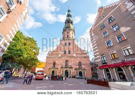 Riga, Latvia - September 23, 2016: View on the famous saint Peter cathedral with colorful tourist bus in the old town of Riga