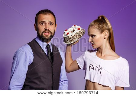 Handsome man in suit and young beautiful brutal girl prepare fight with cake over purple background.
