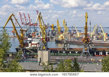 ODESA UKRAINE - JULY 14 2015: Lifting cargo cranes ship and grain dryer in Sea Port of Odessa Black Sea Ukraine. Odessa Marine Trade Port is the largest Ukrainian seaport and one of the largest ports in the Black Sea basin
