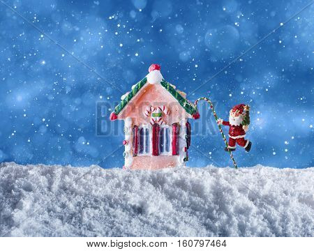 Cute puppet of Santa Claus wishes merry christmas on the snow with candy house