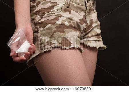 hand with a bag of drugs at a pocket