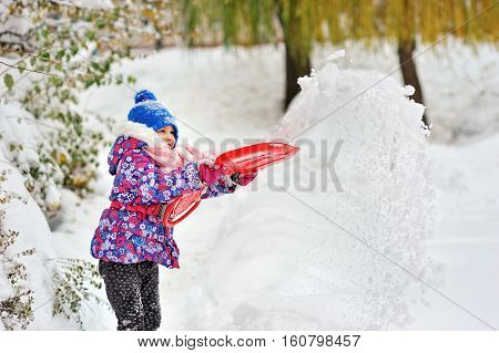 little happy girl playing toss up snow from the pan