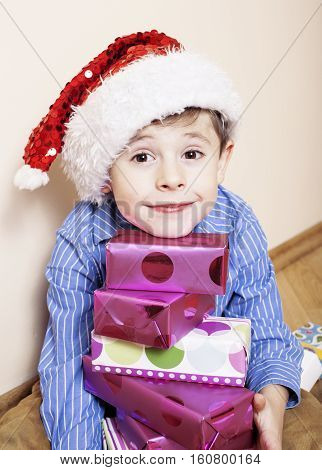 little cute boy with Christmas gifts at home. close up emotional face on boxes in santas red hat. mischief