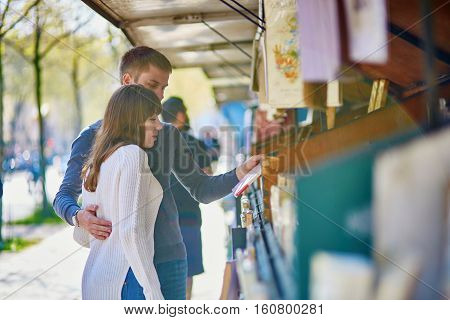 Romantic Couple In Paris Selecting A Book From A Bookseller