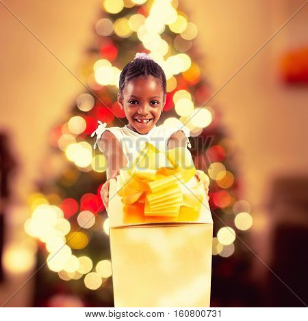 Happy little girl receives a big golden xmas gift and on background lights of the Christmas tree