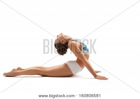 Flexible female gymnast doing acrobatic exercise, isolated on white background. Young athletic girl in bright leotard practicing in gymnastics