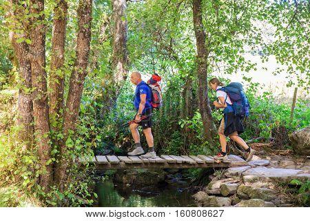 SAMOS, SPAIN - AUGUST, 11: Two pilgrimns crossing foot the little bridge on the creek on August 11, 2016