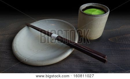 Traditional cup of green tea and blank plate with chopstick on wooden table