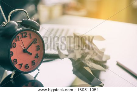 Business deadline failure concept. A scrubbed paper is place on the table as the office worker failed to finish work on deadline on the clock.