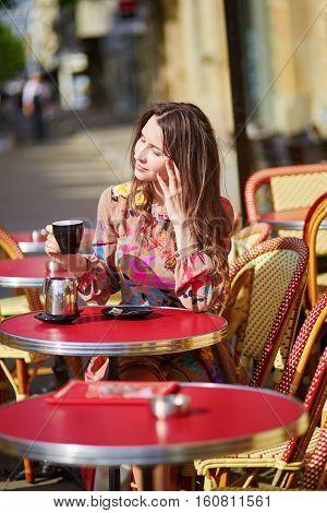 Beautiful Young Woman In A Parisian Street Cafe
