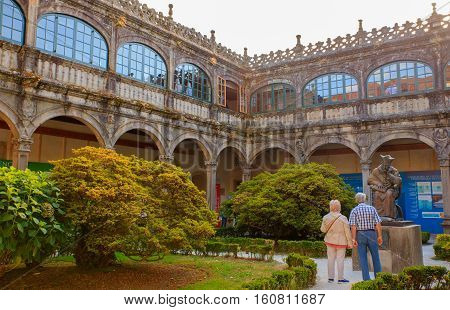 SANTIAGO SPAIN - AUGUST 17: Couple of tourists looking the monument in the Inner court of library of university on August 17 2016