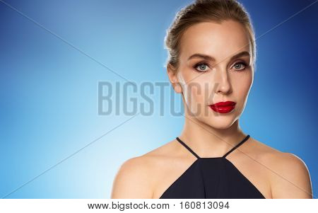 people, luxury and fashion concept - beautiful woman in black with red lips over blue background