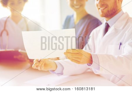 hospital, cardiology, people and medicine concept - close up of happy doctors looking at cardiogram at medical office