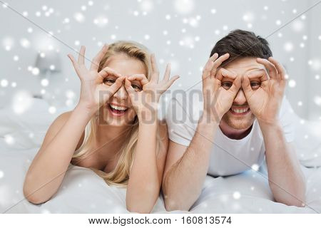 people, christmas, winter holidays, love and fun concept - happy couple lying in bed at home and making finger glasses over snow