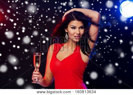 people, winter holidays, party, night lifestyle and leisure concept - beautiful sexy woman in red dress with champagne glass dancing at nightclub over snow