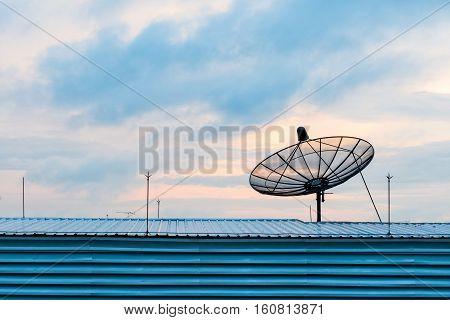 Satellite dish transmission data on background sunrise