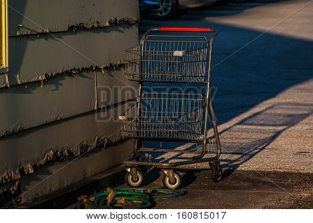 Shopping cart abandoned near an old building